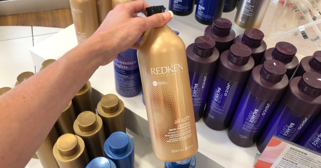 hand holding redken all soft shampoo