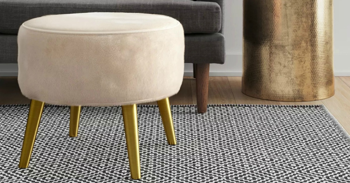 White suede ottoman with gold legs in living room set up