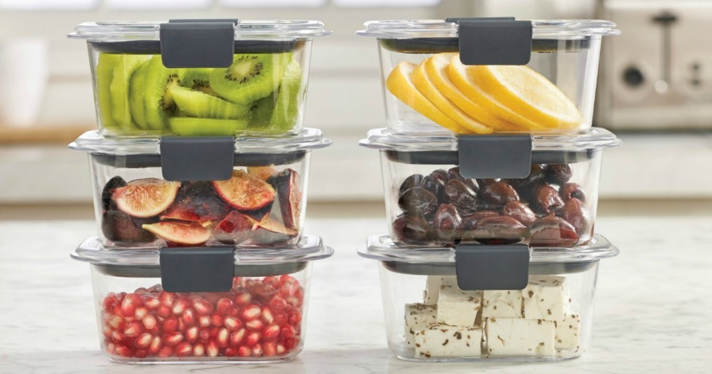 Food storage containers with fresh fruit, olives, and cheese inside on a counter top