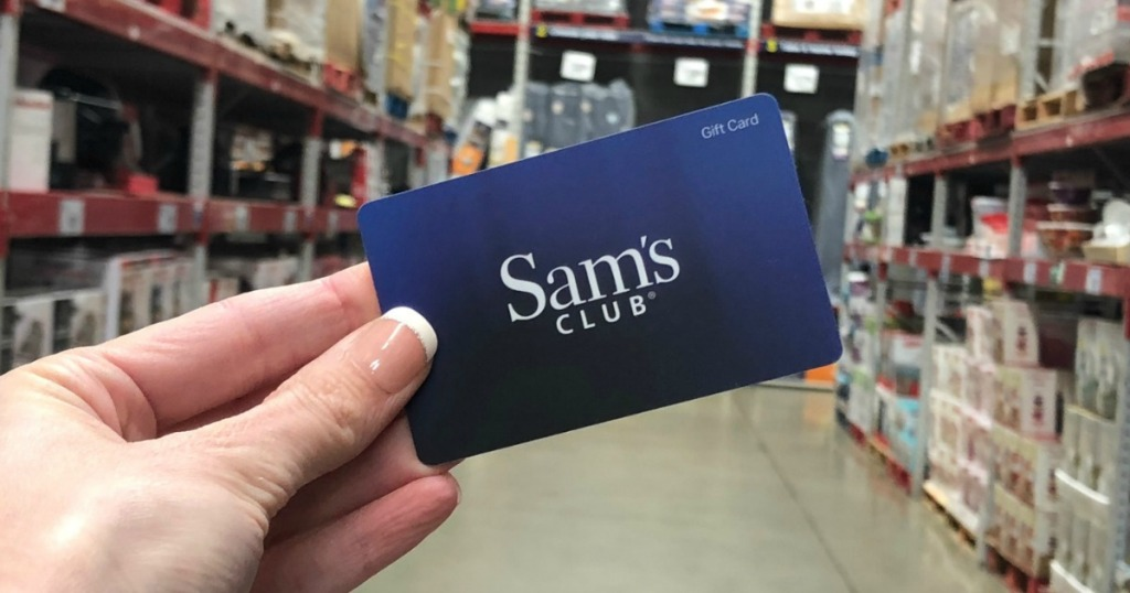 Hand holding Sam's Club gift card in store