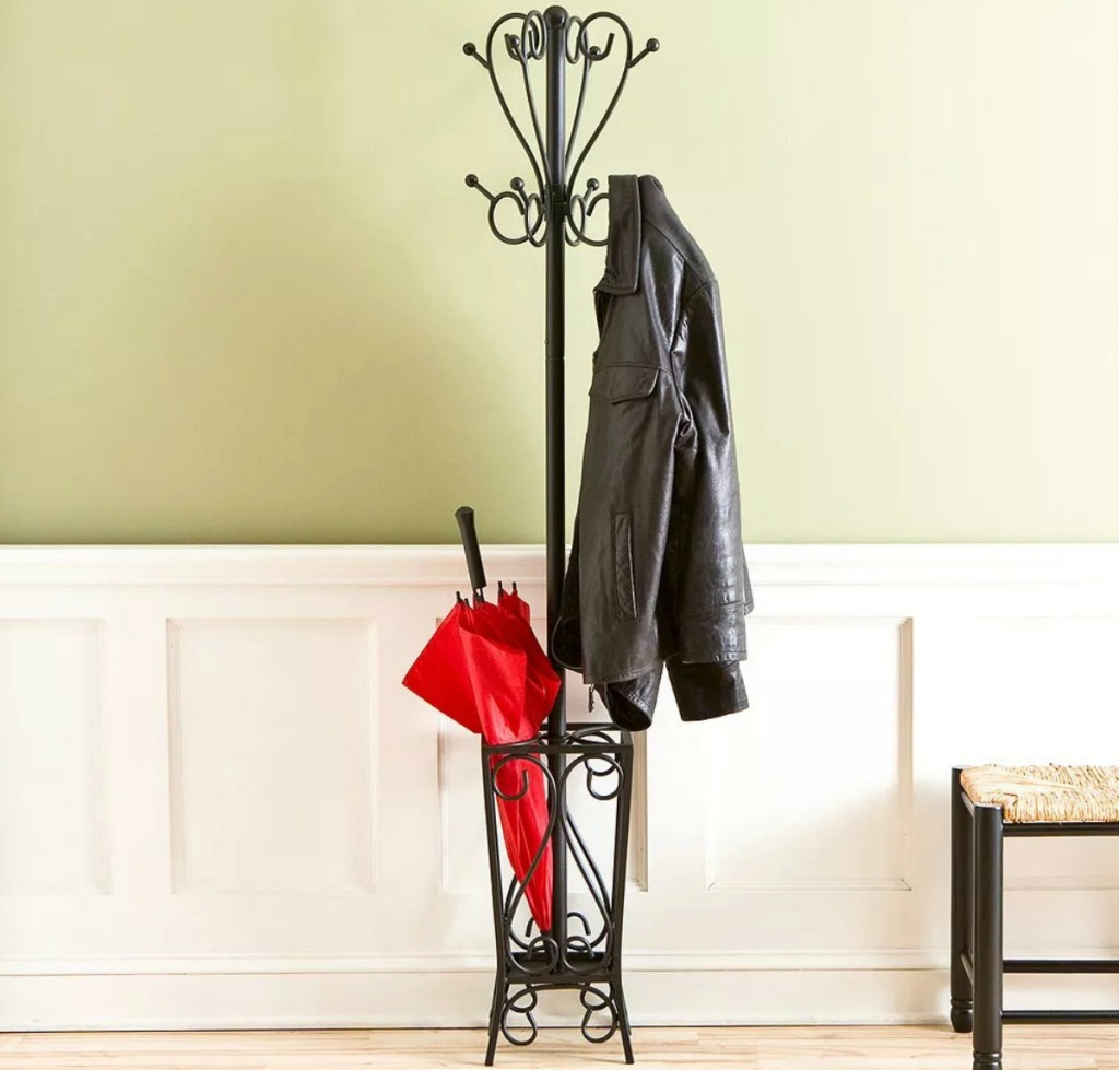 Black metal coat rack with built-in umbrella stand with leather jacket and red umbrella