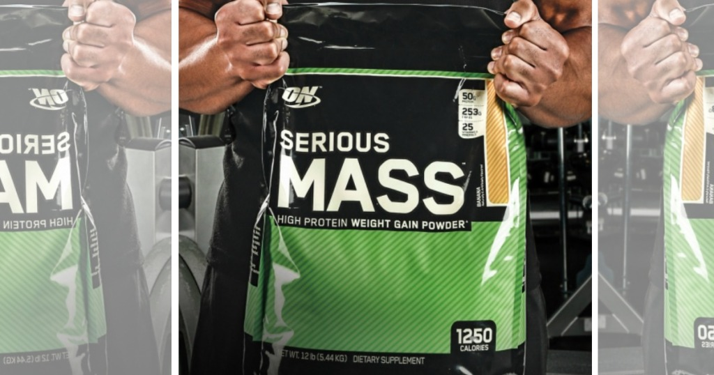man holding bag of 12-pound bag of Optimum Nutrition Serious Mass Weight Gainer Protein Powder in gym
