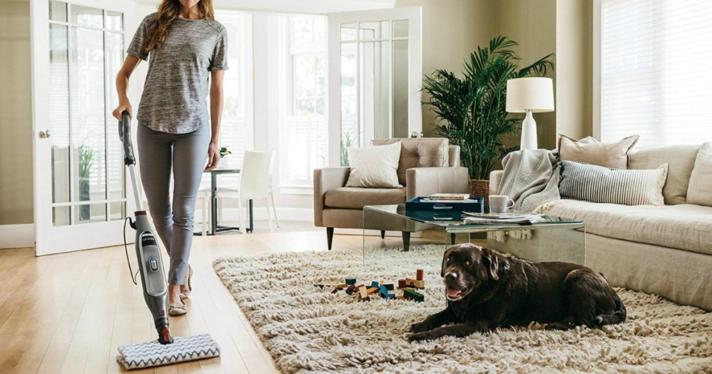 woman using a Shark Genius Pocket Steam Mop in her living room with her dog