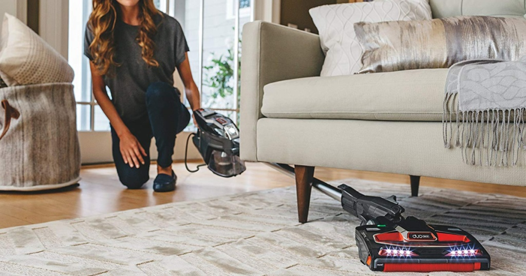 woman using shark vacuum under couch on rug