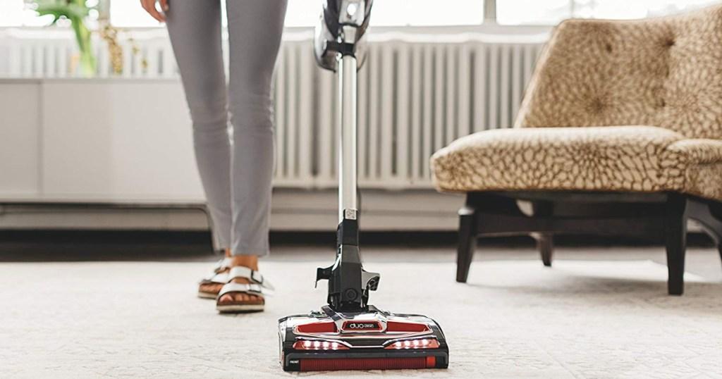woman using shark vacuum on carpet
