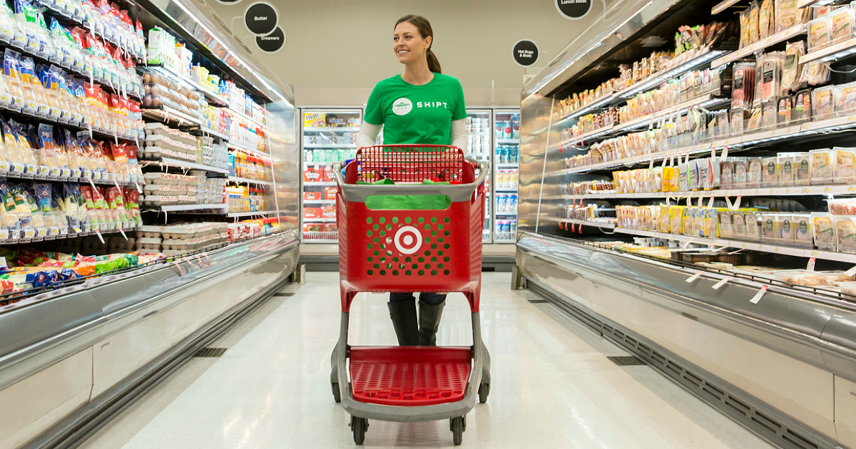 Woman in Shipt tee pushing Target shopping cart in aisle