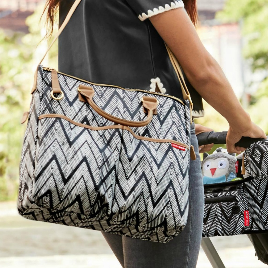 Zig-zag black and white printed diaper bag on woman shoulder while pushing a stroller with coordinating accessories