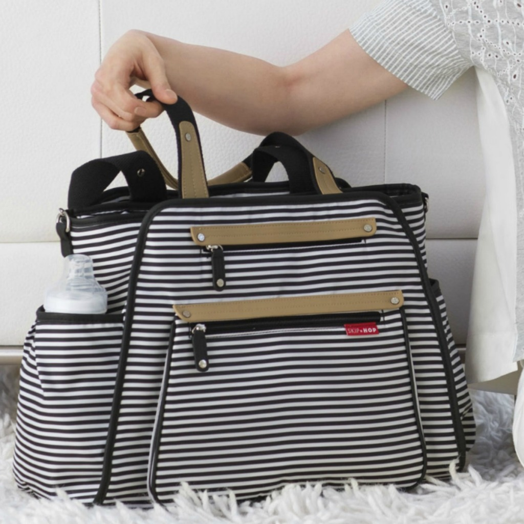Black and white stripped diaper bag on white faux fur rug near white couch