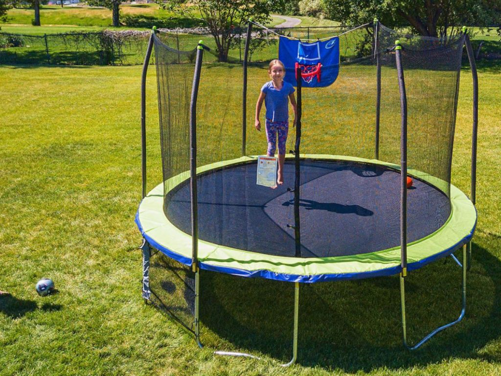 girl jumping on Skywalker 12' Round Sports Arena Trampoline with Enclosure