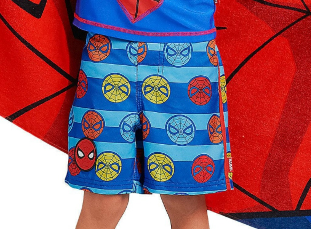Boy wearing spider-man themed swim trunks while holding a Spider-man towel
