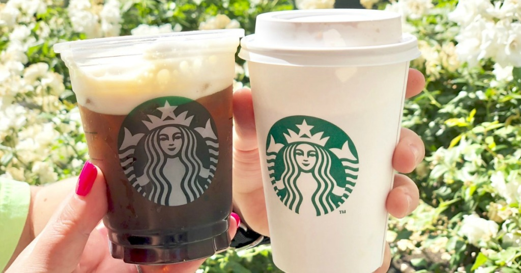 holding two Starbucks beverages