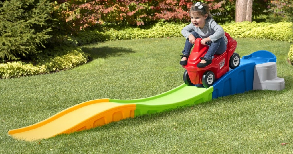 Young girl rides on a roller coast toy in grass filled yard