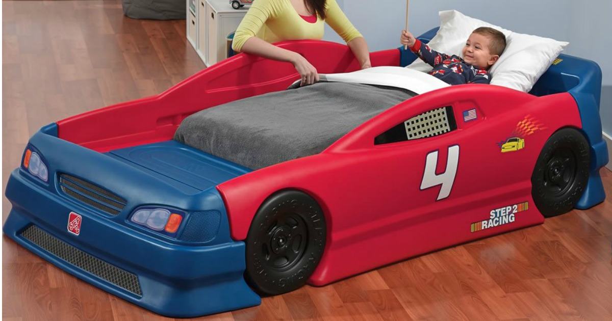 toddler boy lying down in Step2 Stock Car Convertible Bed