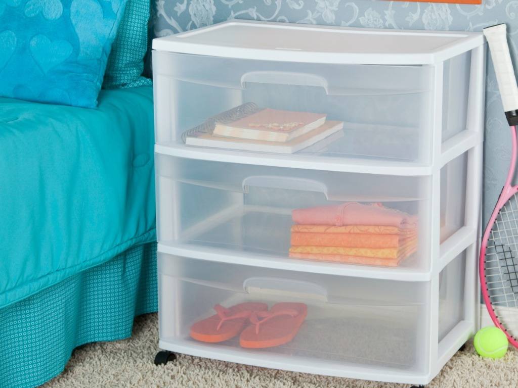 white plastic shelf next to bed with teal covers