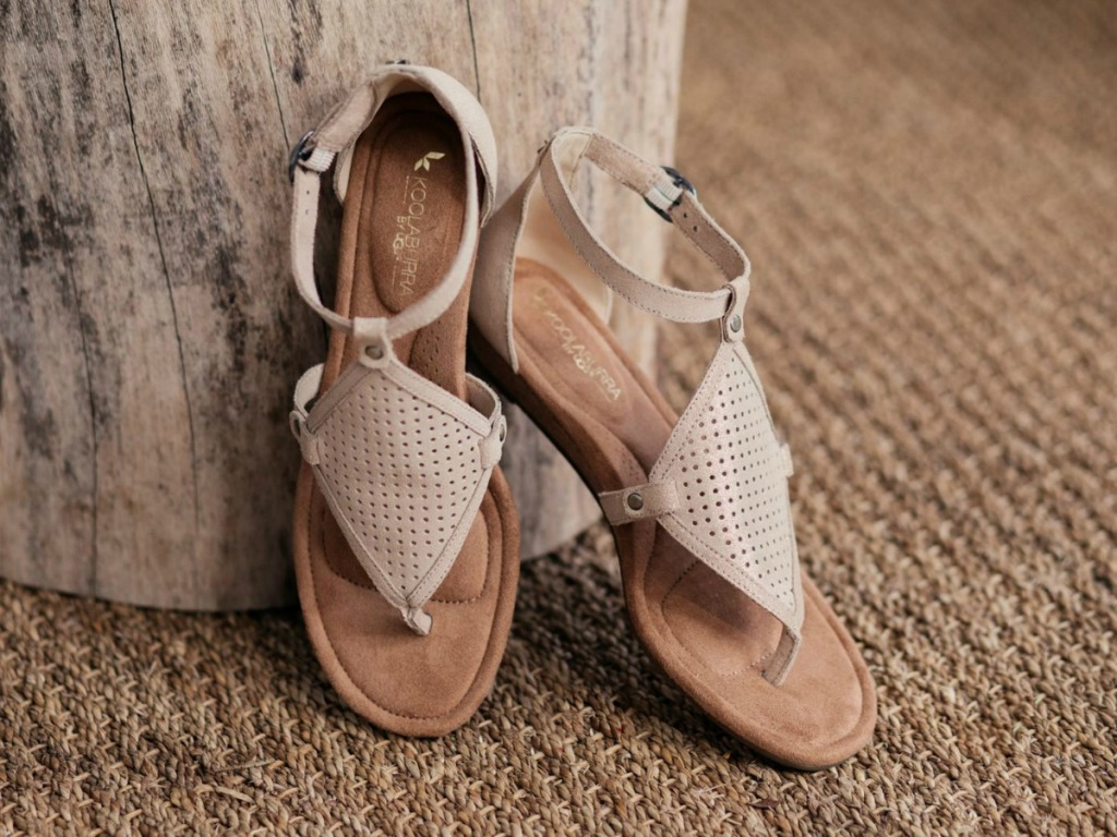 tan sandals resting against a wood stum