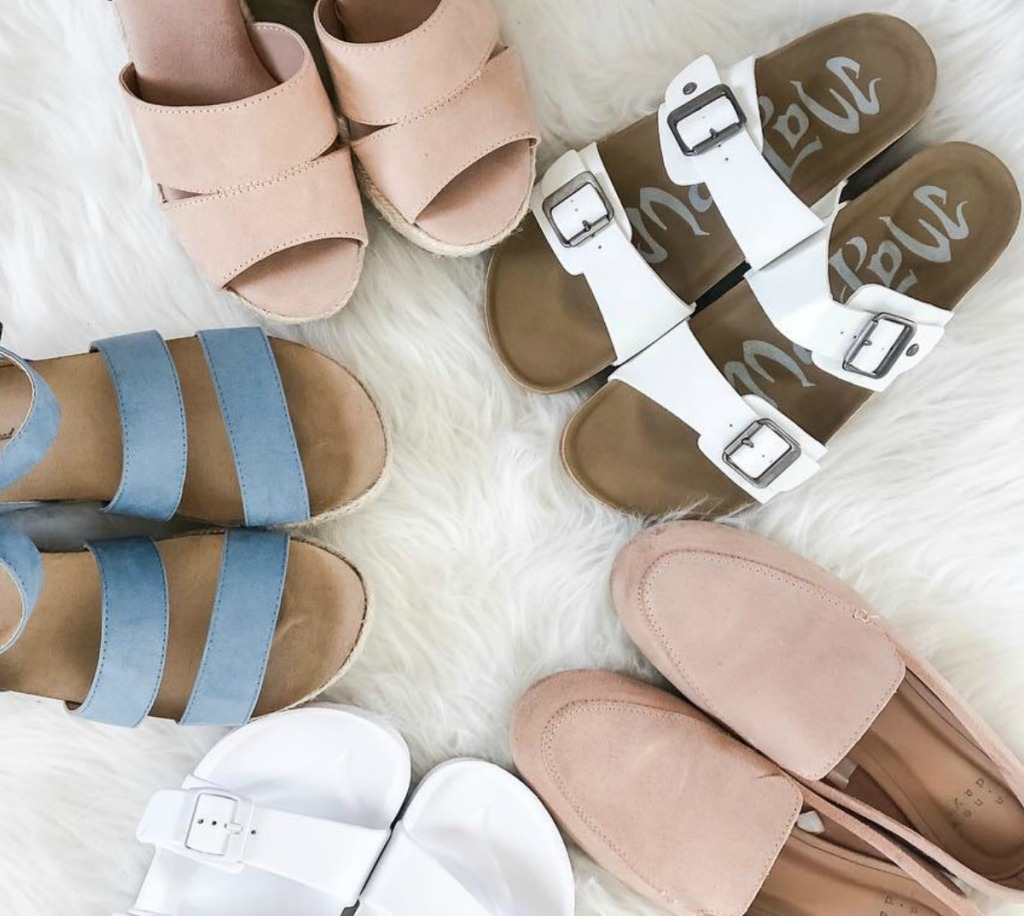 Various styles of women's shoes on white fur carpet