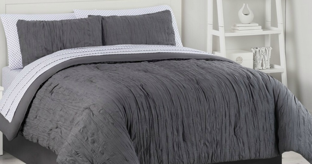 bed with a dark grey crinkle bedding set on it
