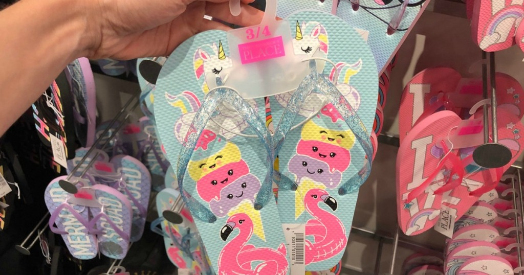 lady holding The Children's Place flip flops at the store