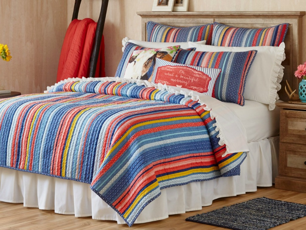 striped quilt on bed in bedroom
