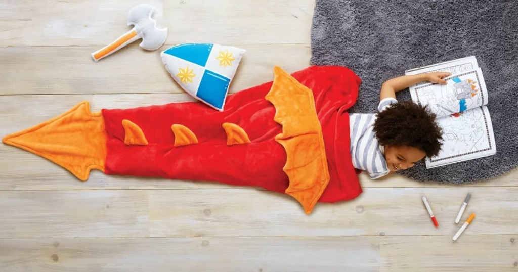 Boy laying on grey fur rug with dragon tail wearable blanket