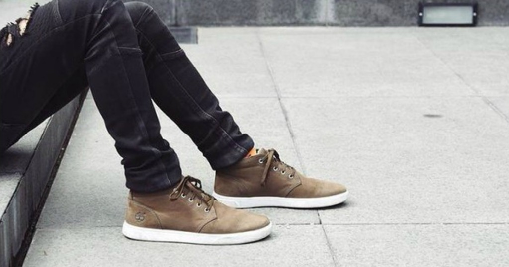 Man sitting on sidewalk wearing Timberland Chukka Boots