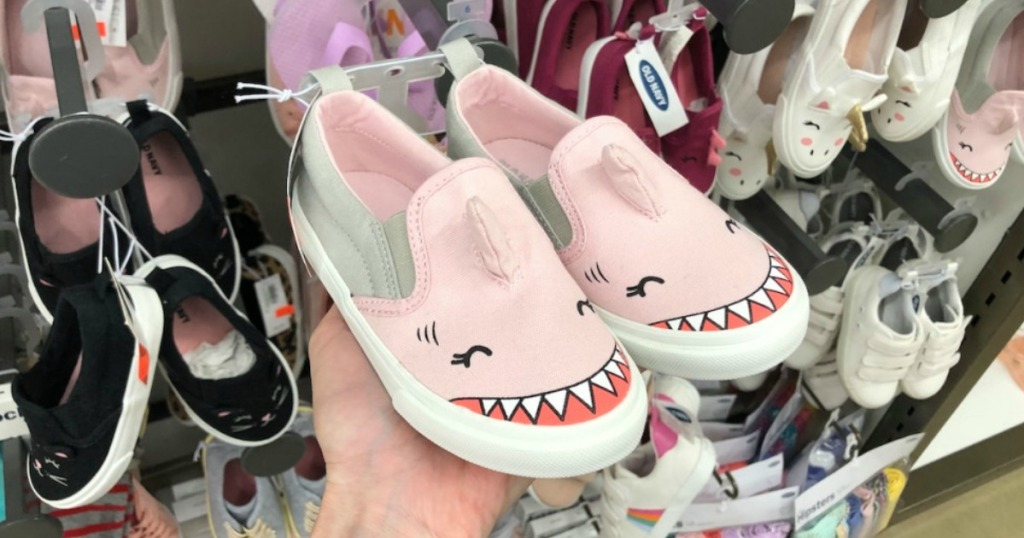 Someone holding up a pair of Toddler Shark Sneakers at Old Navy