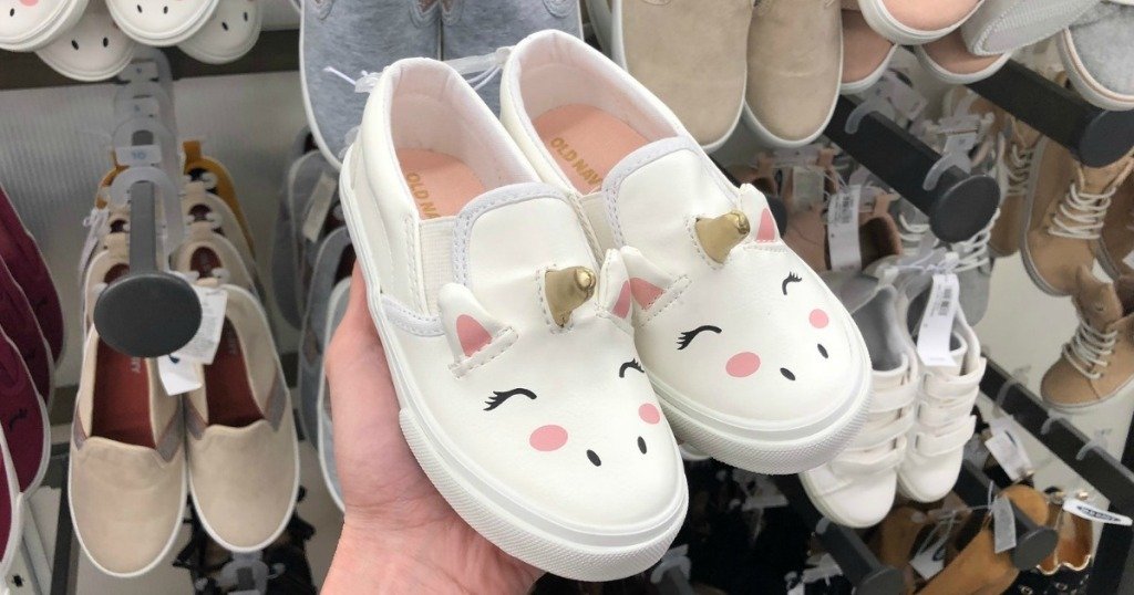 Woman holding a pair of Toddler Unicorn Sneakers at Old Navy