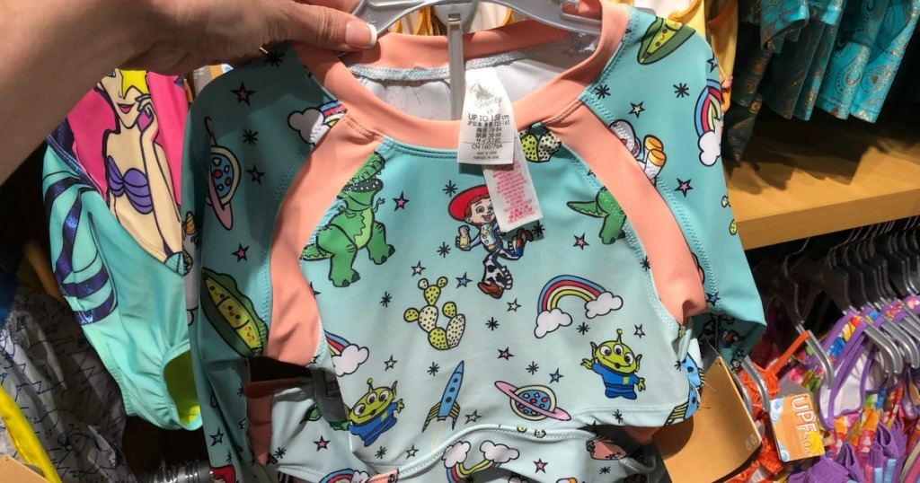 woman holding Toy Story 2-piece swimsuit