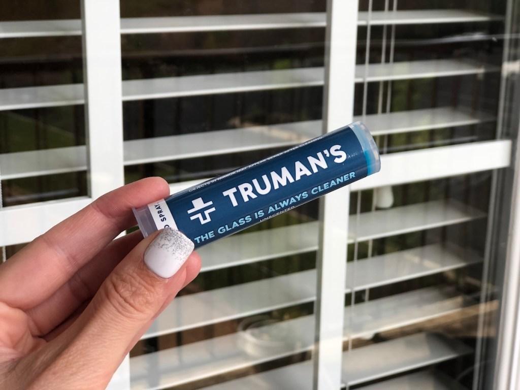 hand holding Truman's glass cartridge near window