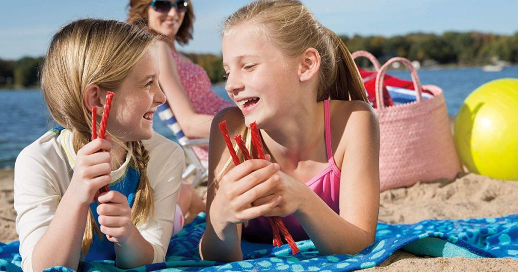 girls eating twizzlers on beach