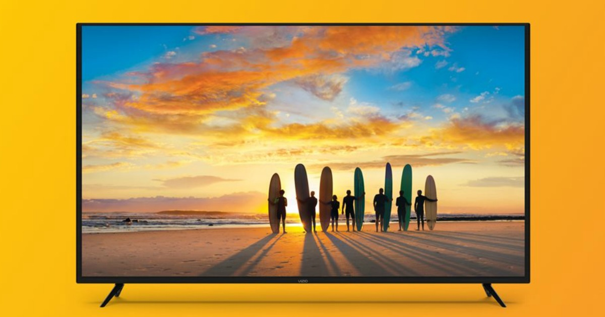 big screen tv showing surfboards and surfboarders on a beach with a beautiful sunset
