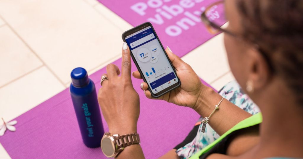 woman holding phone with Weight Watchers app and yoga mat