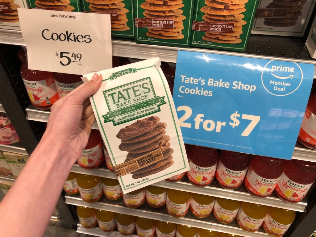 hand holding whole foods tate bake shop cookies in front of sale sign at whole foods