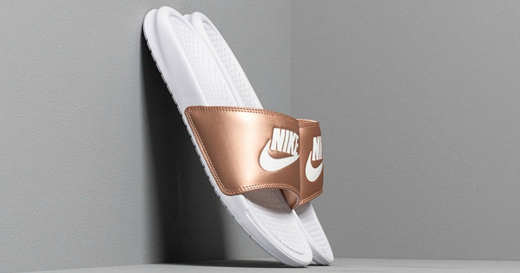 Women's Nike Benassi JDI Slide leaning against a gray wall