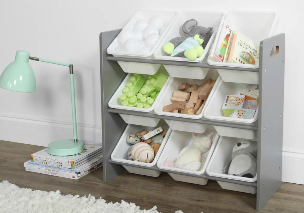 Gray toy storage compartment with nine white bins in a nursery