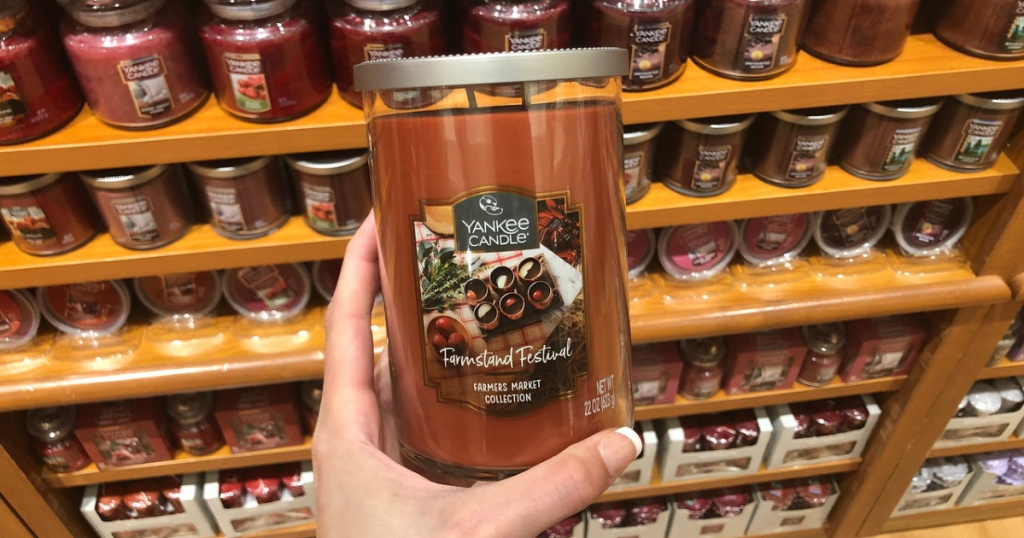 woman holding yankee tumbler candle in store
