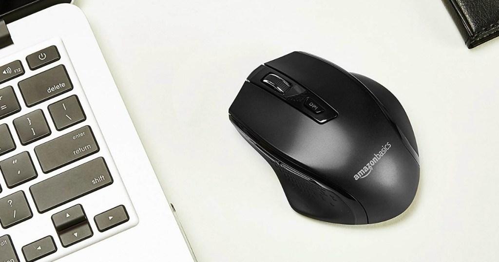 Black Wireless Mouse on desktop near PC