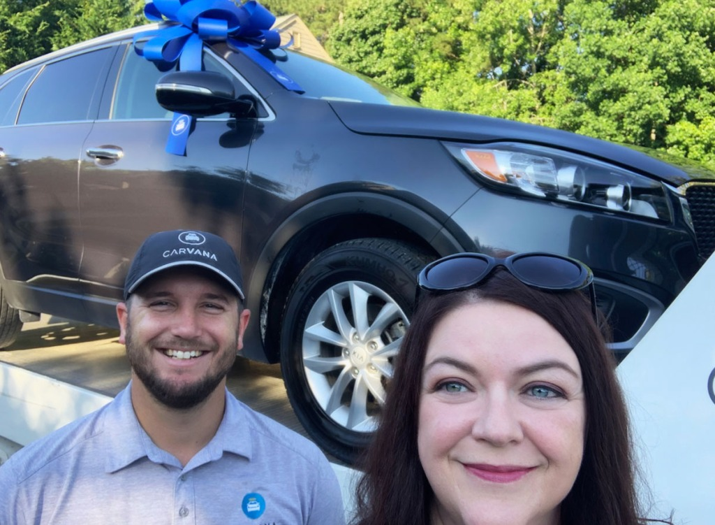 woman and man standing in front of a car at carvana dealership