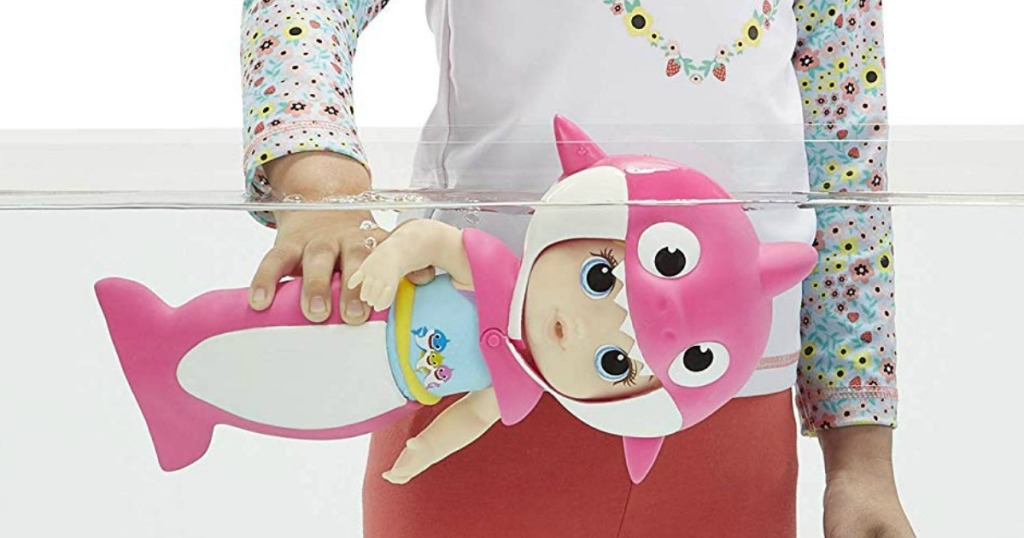 girl playing with a baby alive baby shark doll