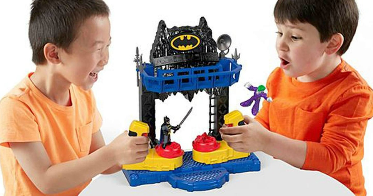 two little boys play with batman toy at table