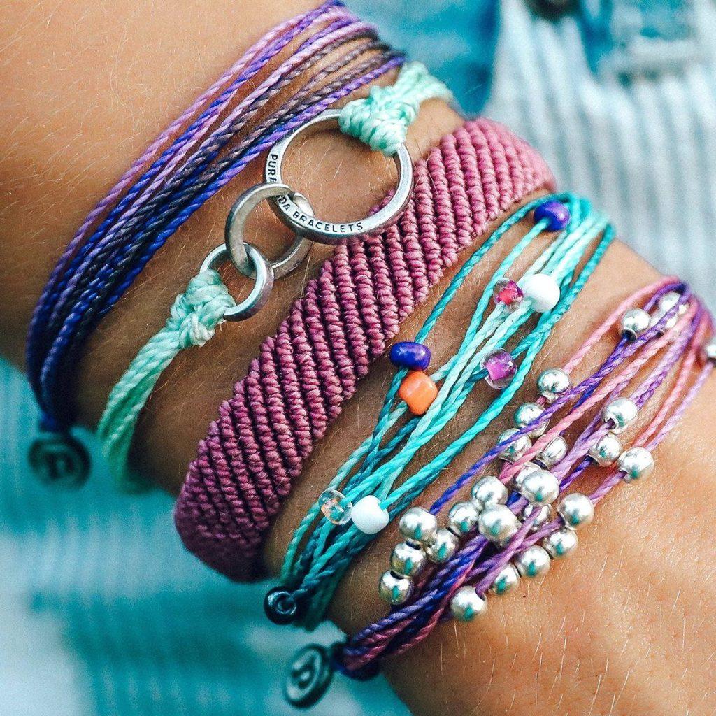 Woman wearing Pura Vida bracelets in purple and teal colors