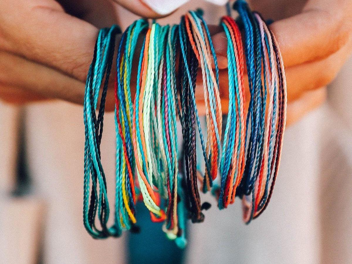 woman holding bestie pack of bracelets from pura vida