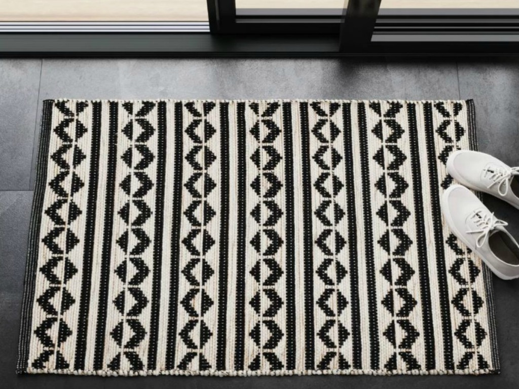 black and white rug by door with a pair of shoes next to it