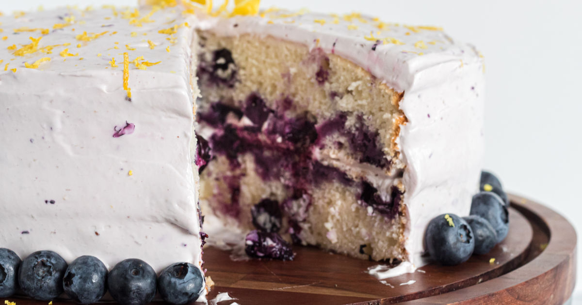 closeup of the baked, frosted, blueberry lemon cake with a slice out of it