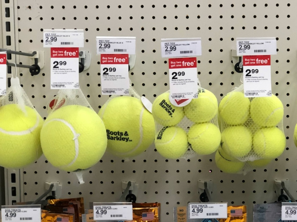 yellow balls that are pet toys hanging on store display