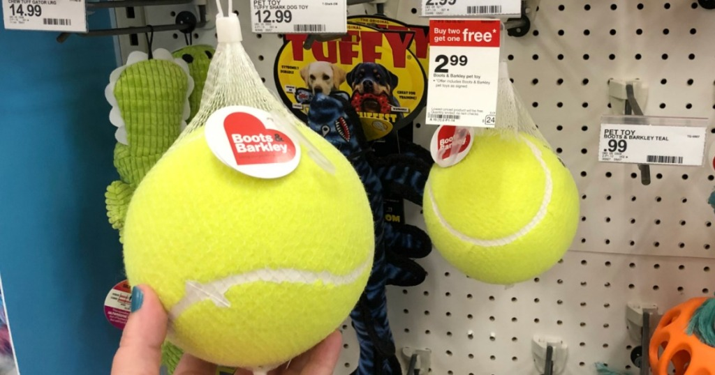 hand holding large yellow tennis ball by store display