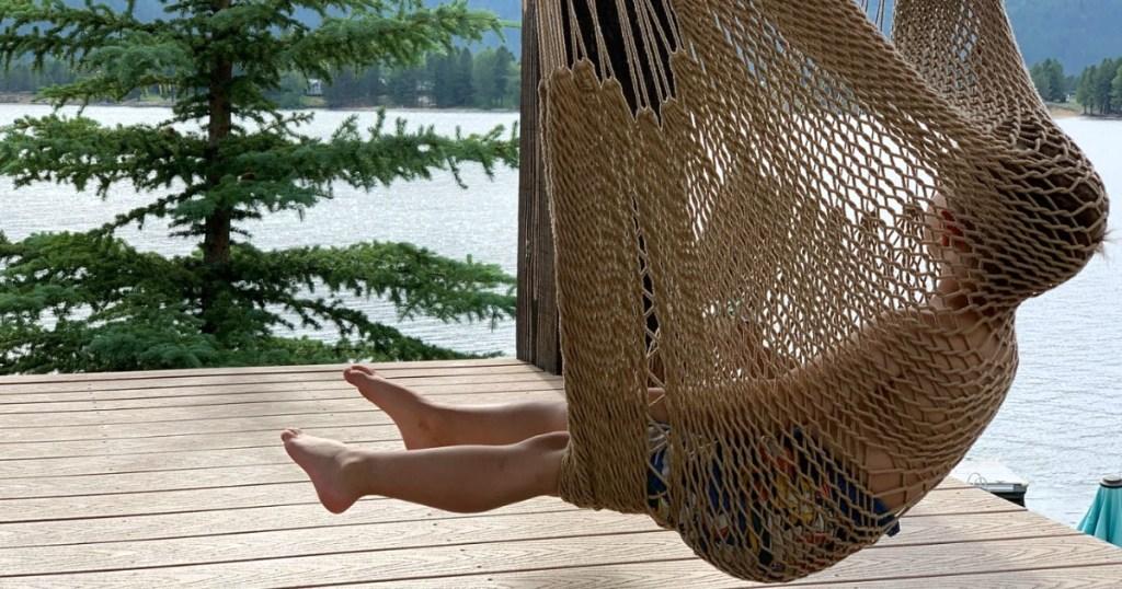 little boy in hammock chair swinging outside
