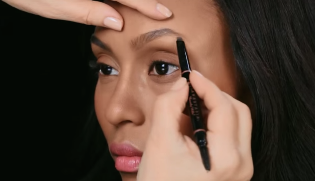 woman getting her eyebrows filled with brow pencil