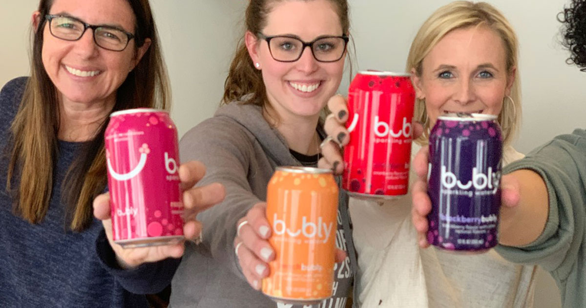 girls holding bubly sparkling water cans