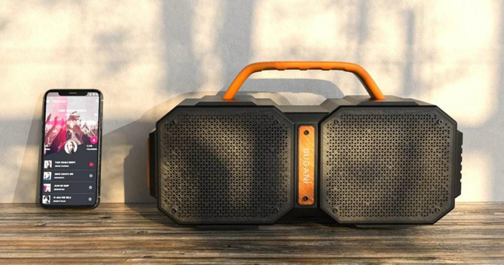 orange and black speaker with phone sitting beside it